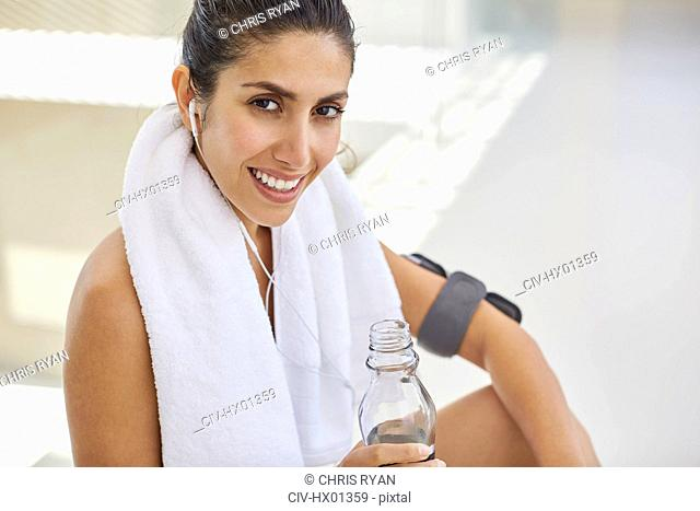 Portrait smiling woman with towel and water bottle listening to music with headphones post workout