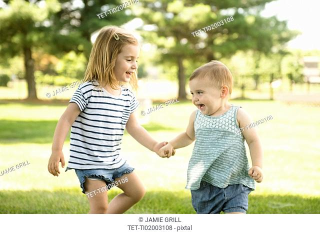 USA, Pennsylvania, Washington Crossing, Two sisters (18-23 months, 2-3) holding hands and walking together