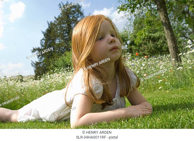 Girl laying on grass in field of flowers