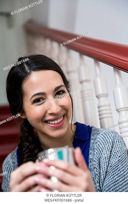 Portrait of smiling woman in staircase holding cup of coffee