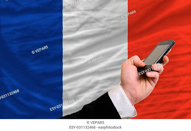 man holding cell phone in front national flag of france symbolizing mobile communication and telecommunication