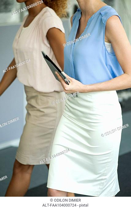 Businesswoman walking with colleague, carrying digital tablet
