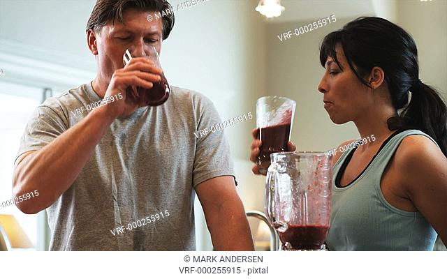 mature couple standing in the kitchen sharing a smoothie