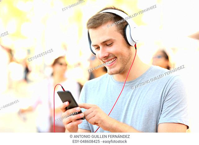 Happy boy listening to music and selecting a song walking on the street