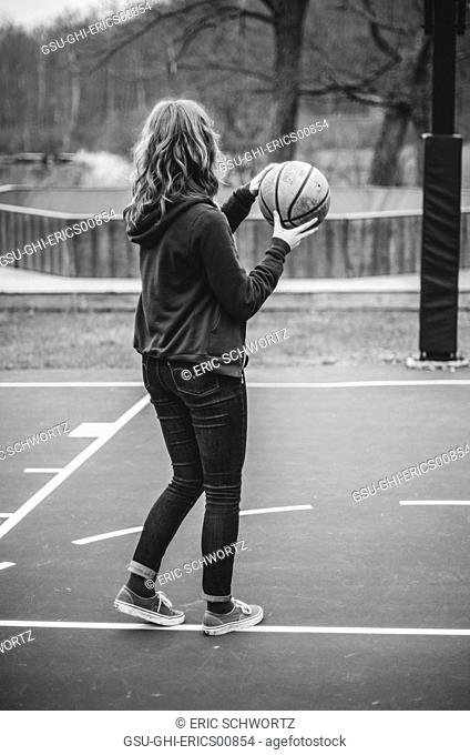 Young Woman in Jeans and Hooded Sweatshirt Holding Basketball
