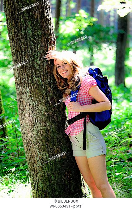 Woman in nature while hiking.Leaning against a tree