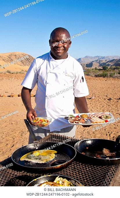 Namibia Africa Northern Desert of Namib Desert border of Angola and Kunene River safari chef portrait with lunch on river in Hartmann Berge deserted land...