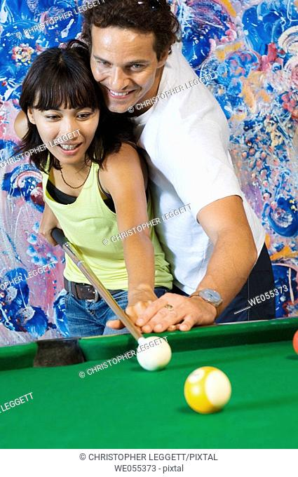 young couple playing billiard