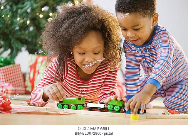 African American brother and sister playing with toy train