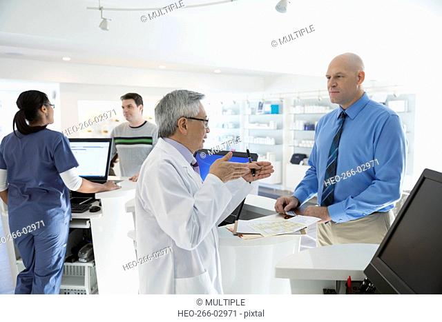 Doctor explaining to patient in clinic lobby
