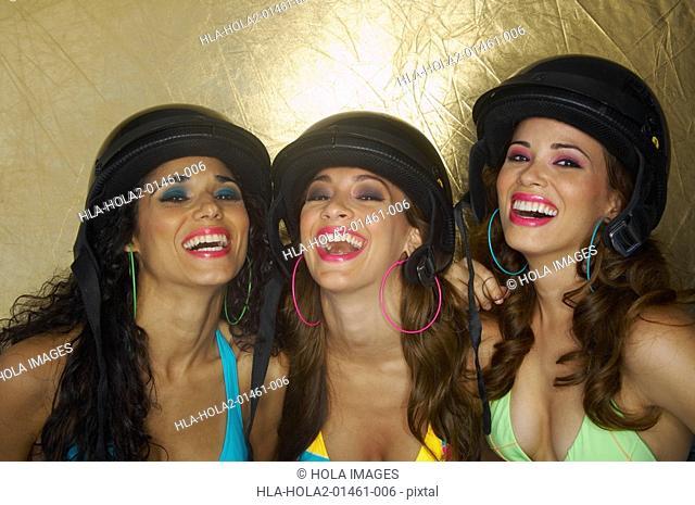 Three sexy young women wearing helmuts