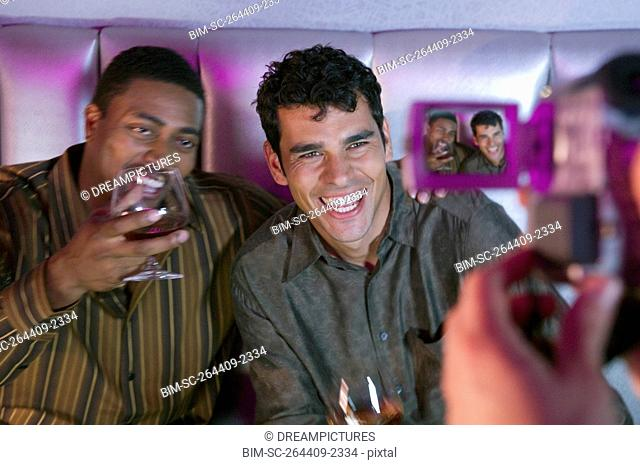 Two men with drinks being video recorded