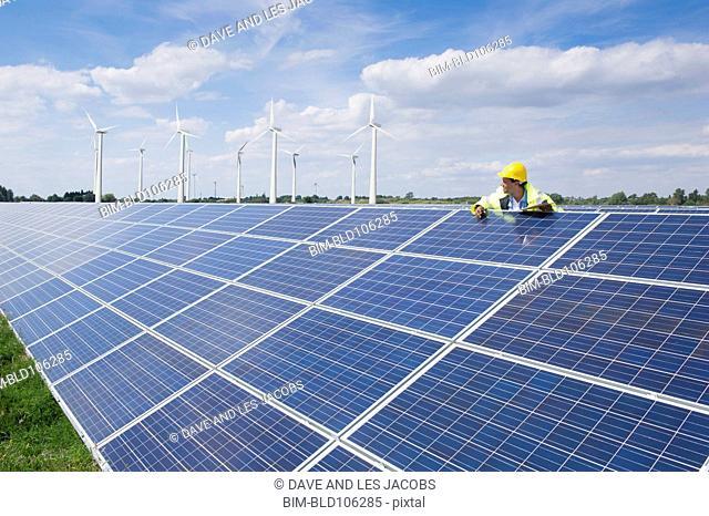 Mixed race man checking solar panels