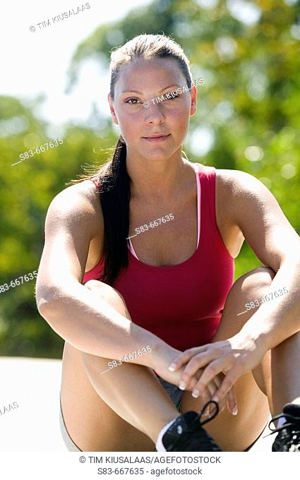 Athletic woman sitting on ground