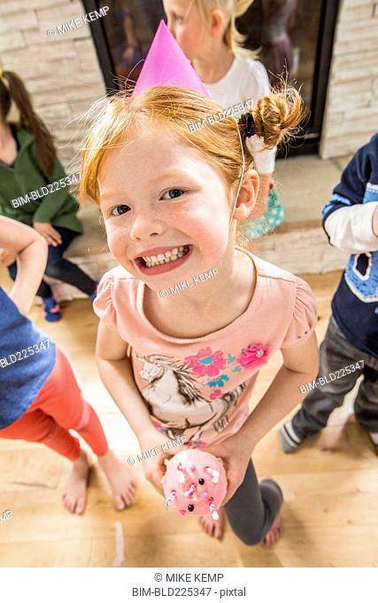 Caucasian girl wearing party hat holding cupcake