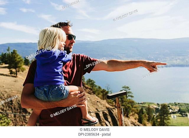 A father holds his young daughter as they look out over Lake Okanagan; Peachland, British Columbia, Canada