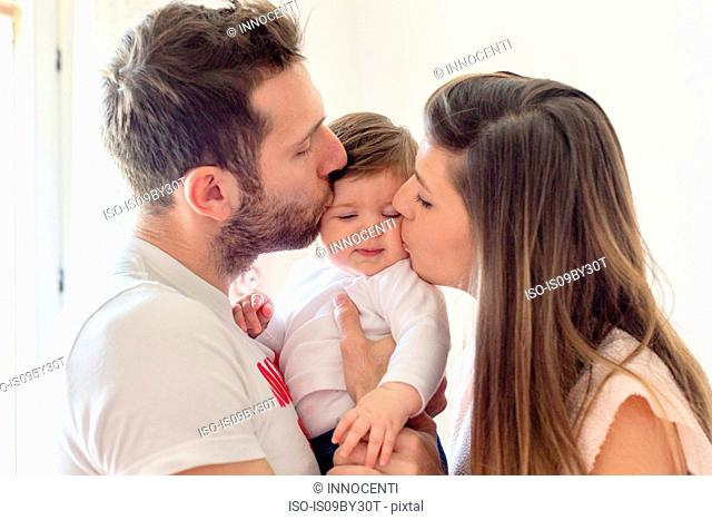 Parents kissing baby girl's cheeks at home