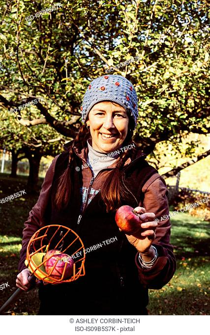 Portrait of woman holding fruit picker and fresh apple