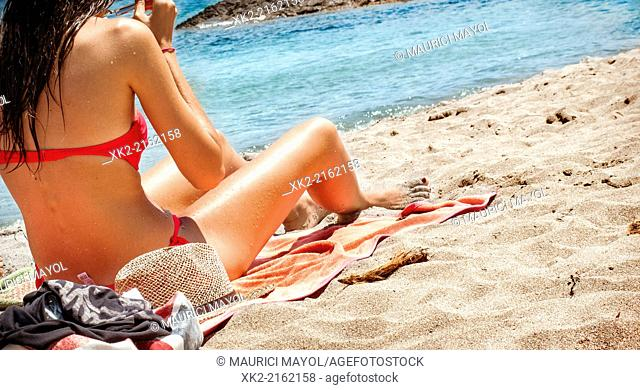 Brunette woman in bikini under the sun in a Menorcan blue beach