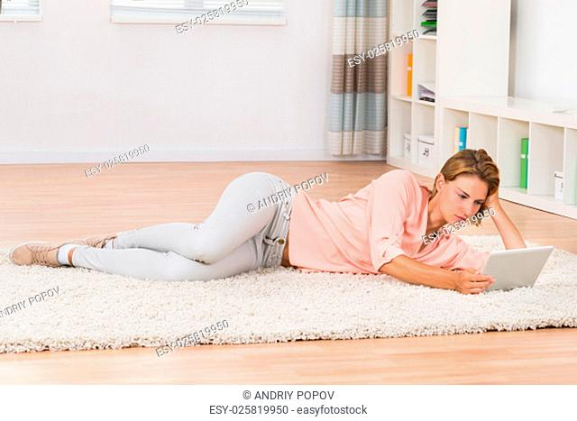 Beautiful Young Woman With Digital Tablet Lying On Carpet