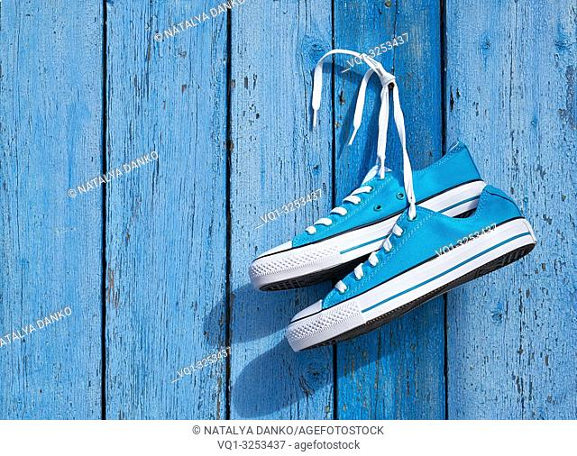 pair of blue textile sneakers hanging on a nail on the wall of old cracked wooden planks, copy space