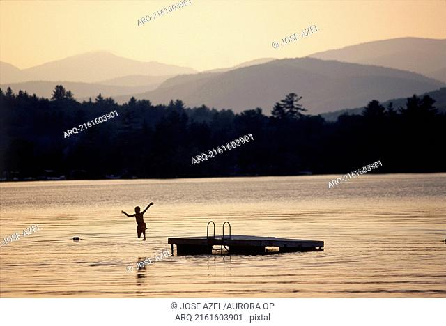 A young boy jumps into the lake from a dock, Maine, USA