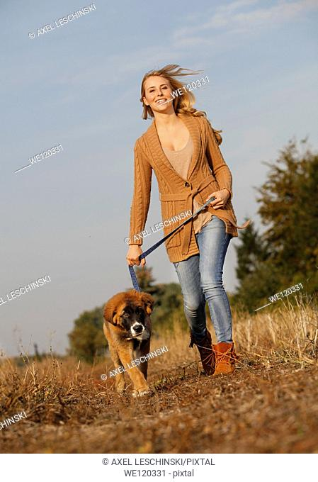 Woman walking with dog in landscape having fun