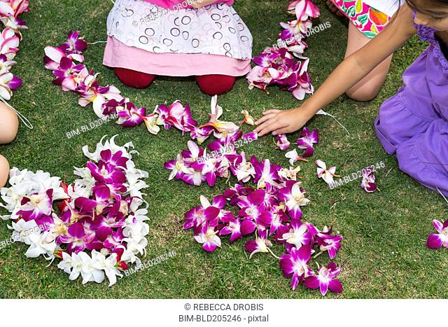 Children playing with flower leis in grass