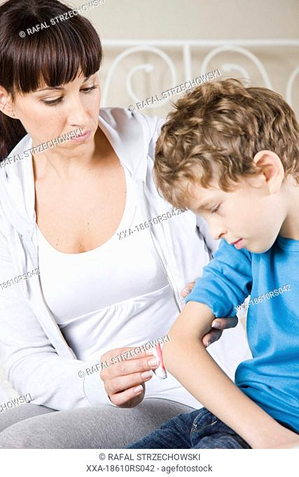 mother disinfecting wound on son elbow