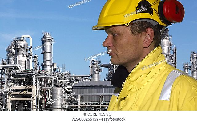Person wearing safety clothing, talking in a walkie talkie, with a petrochemical plant in the background