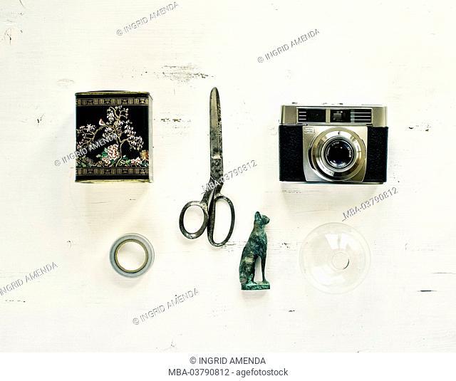 Scissors, camera, tea tin, cat and vase on white table