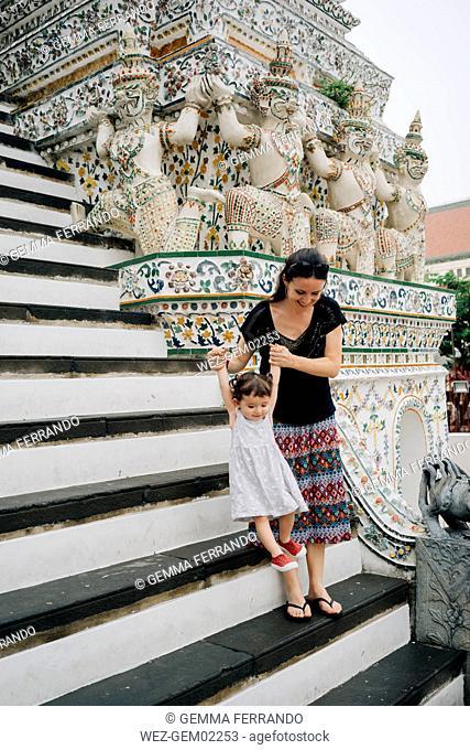 Thailand, Bangkok, Wat Arun, Mother and daughter visiting the Buddhist temple walking downstairs