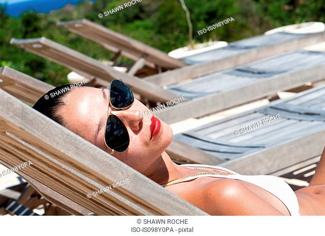 Young woman in sunglasses on lounger