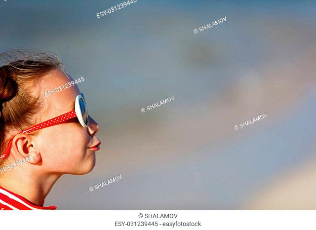Casual portrait of adorable little girl in sun glasses making funny face