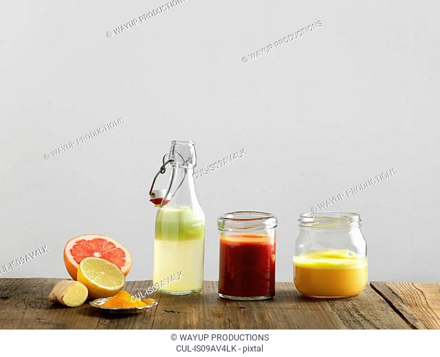 Fruit smoothies in glass bottle and jars, white background