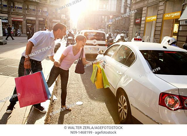 Young couple shopping in Milan, taking taxi