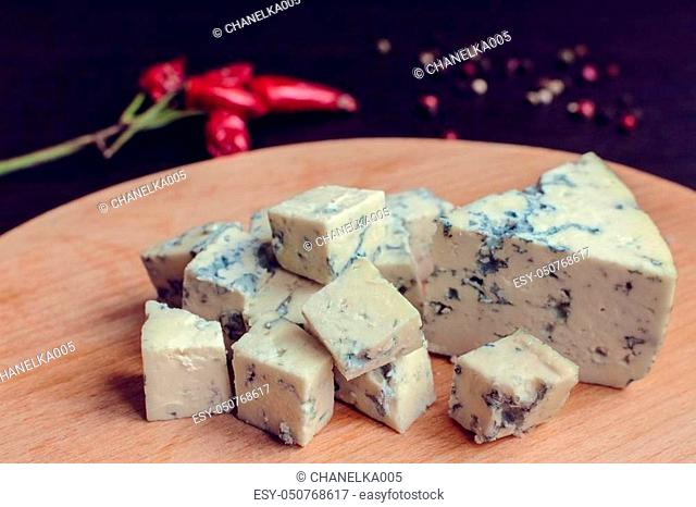 Blue cheese on wooden board. Blue cheese dressing. Bleu cheese. Tasty appetizer. Plate of cheese on wooden plate. Cheese platter. Cheese board