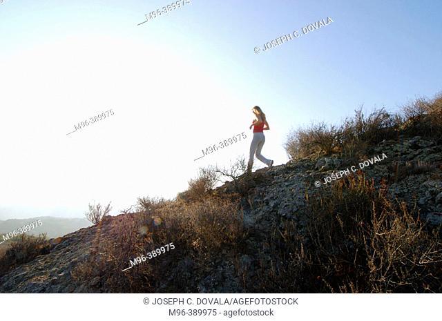 Female jogger down slope in motion