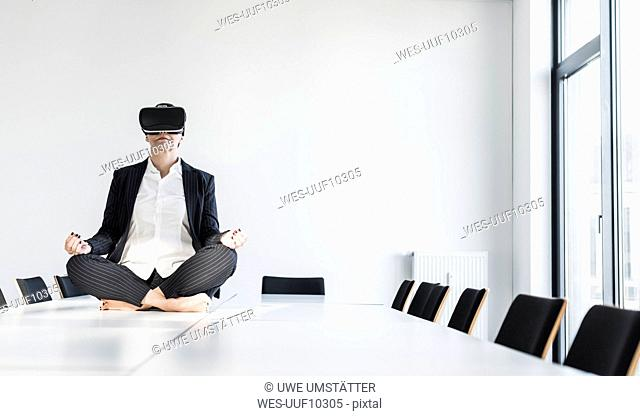 Businesswoman sitting on conference table meditating and wearing VR glasses