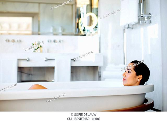 Woman relaxing in bathtub in suite