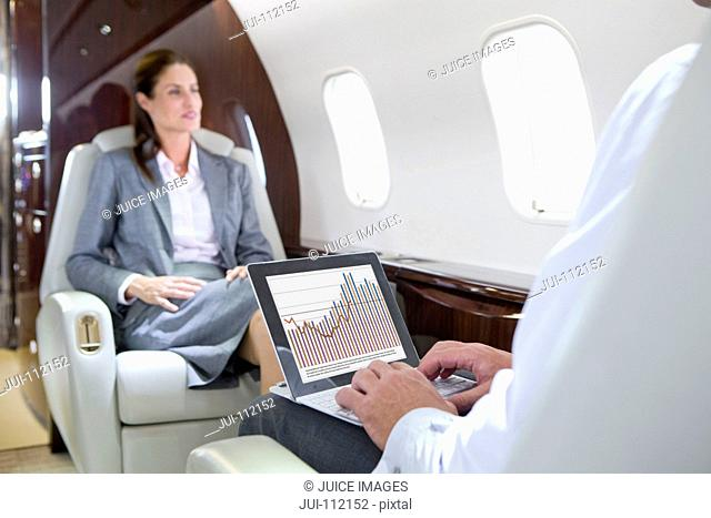 Businesswoman and Businessman with digital tablet having meeting on private jet
