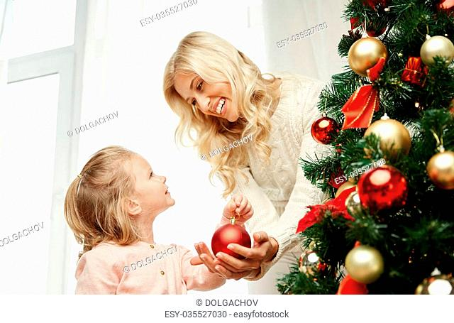 family, x-mas, winter holidays and people concept - happy mother and little daughter decorating christmas tree at home