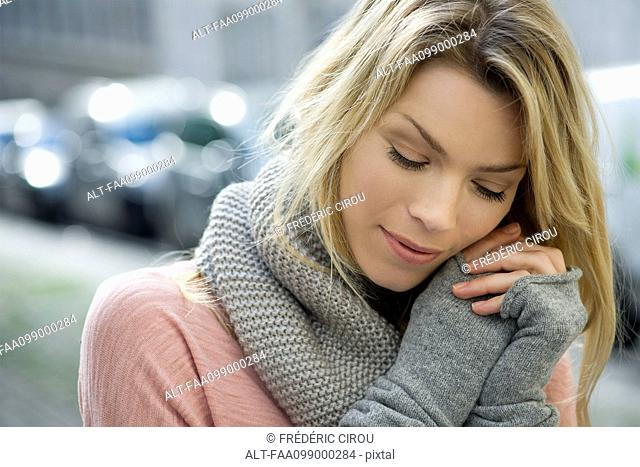 Woman dressed warmly in knit gloves and scarf
