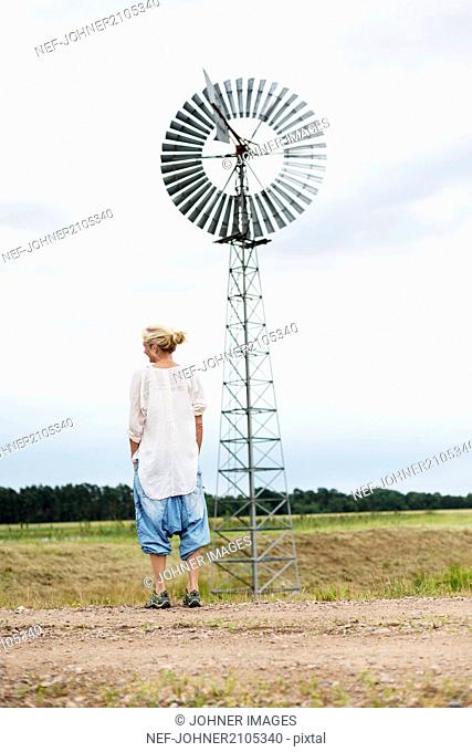 Woman standing next to old-fashioned wind mill
