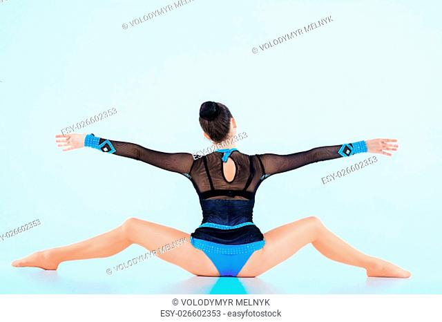 The back view of girl, doing gymnastics dance on blue background