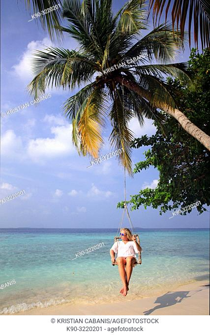 Young caucasian woman sitting in a swing chair, hanging over the beach at a palm tree, Dharavandhoo, Baa Atoll, Maldives, Indian Ocean, South Asia