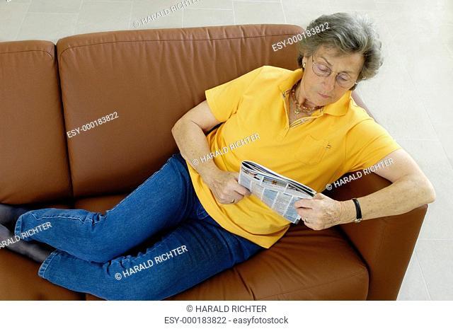 Seniorin auf einer Couch mit TV-Programm