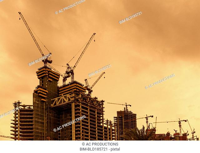 Low angle view of cranes constructing Doha highrise buildings, Doha, Qatar