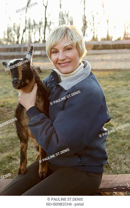 Portrait of mid adult woman holding goat