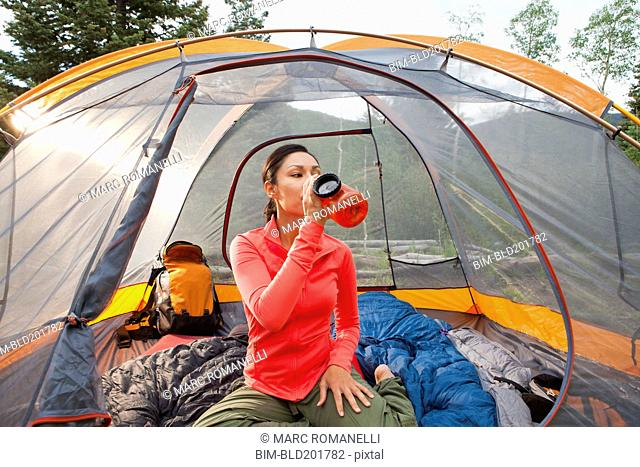 Mixed race woman drinking in tent